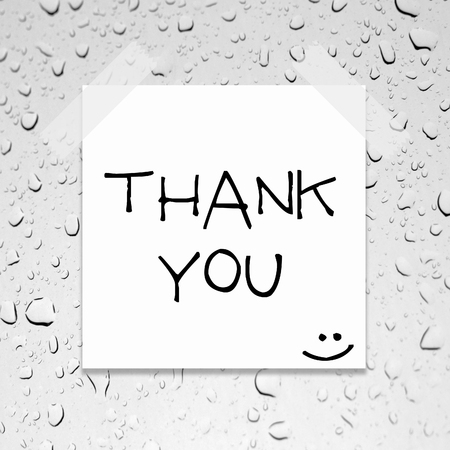 thank you written on piece of paper, on a glass with raindrops background.