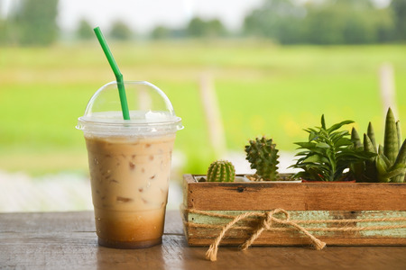 plastic glass of iced coffee on wooden balcony with green nature background Stock Photo