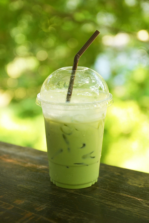 iced milk green tea on wooden table with green nature bokeh background Stock Photo