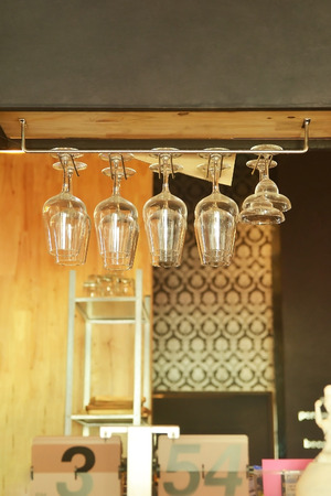 close up wine glass hanging on rack above counter bar