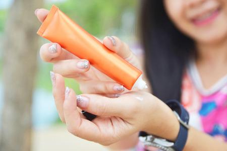 weibliche hände mit sonnencreme uv schutz