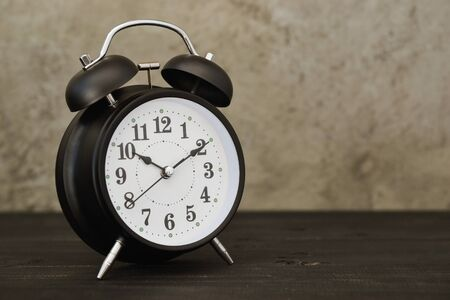 vintage alarm clock on wooden table with cement wall background Stockfoto
