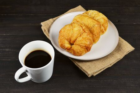 coffee cup and fresh baked croissants on wooden table background