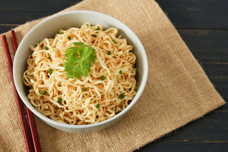 instant noodles in the bowl on wooden table background