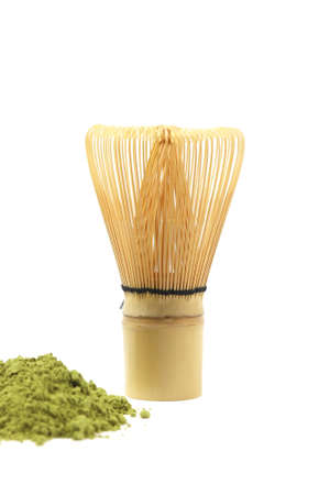 Matcha, green tea powder and bamboo whisk on white background