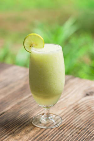 Lemonade smoothie on old wooden table with green nature background Stock Photo