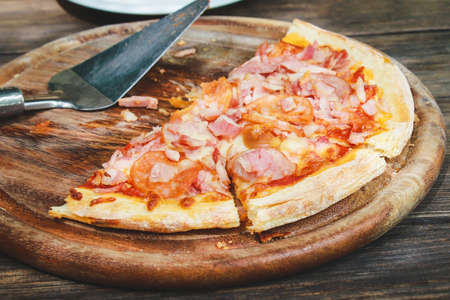 meat lovers pizza with topping pepperoni salami sausage and ham on old wooden table