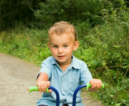 Boy riding bicycle in forest photo