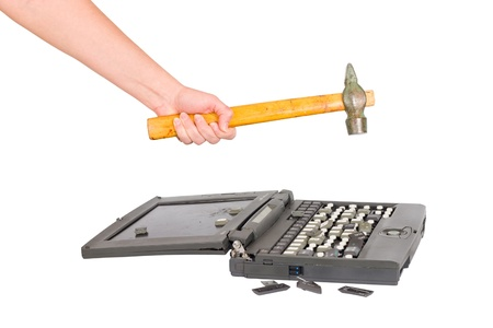 hand with a hammer destroys laptop photo
