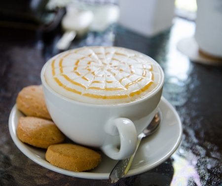 a cup of hot cappuccino with biscuit
