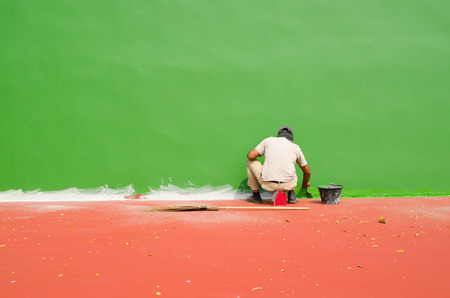 paint roller: Asian man With Paintbrush and green blank wall