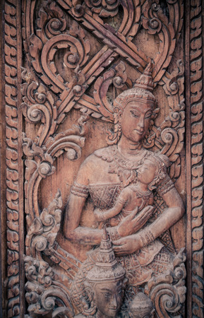 Wood carvings, mother and children, on a door of Thai temple. photo
