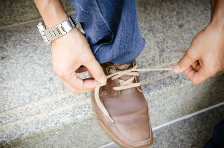 a Man lacing his suede shoes photo