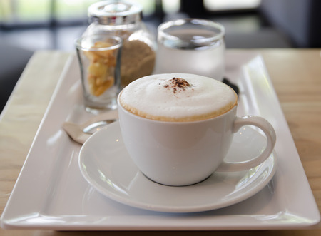 Cappuccino coffee cup with sugar, biscuit  and drinking water
