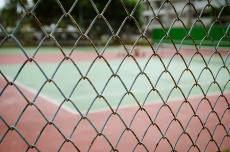Wire fence with tennis court on background