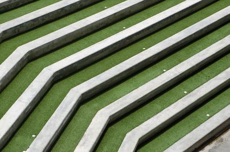 grandstand: Concrete grandstand terrace in a green field.