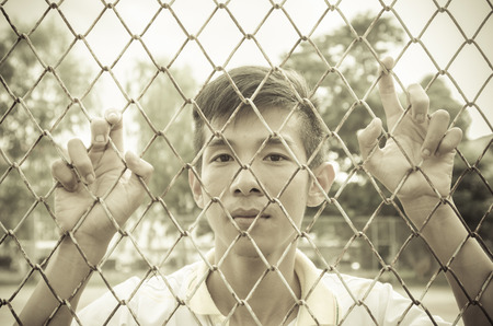 asian young man caged behind metal or steel net