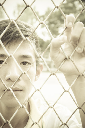 caged: asian young man caged behind metal or steel net