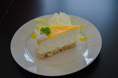 A piece of lemon cheese cake on white plate