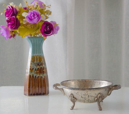 vase: the Moroccan metal bowl placed on a table with a vase of flowers.