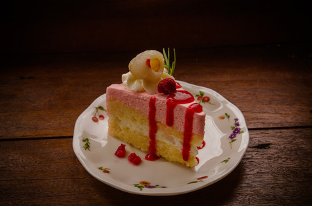 peice of creme cake with litchi on wood table Stock Photo