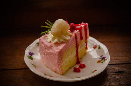 peice: peice of creme cake with litchi on wood table Stock Photo