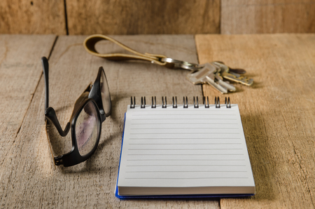 eye pad: Blank line notepad, key chain and eye glasses on wooden table