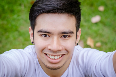 young man portrait: Portrait of a smiling young asian man making selfie photo in park Stock Photo