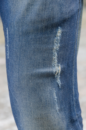 ripped jeans: closeup of blue faded ripped jeans