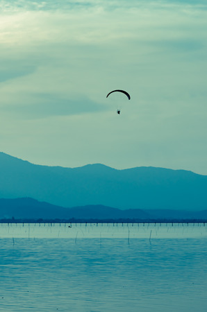 paraglider: Silhouette paraglider on sunset sky background
