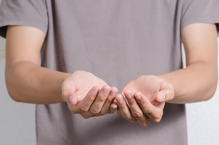 two persons only: Young man offer hand and holding nothing. hands as if holding someting isolated on white