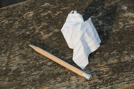 the crumpled note paper and used pencil on wood background Stock Photo