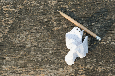 wastrel: the crumpled note paper and used pencil on wood background Stock Photo