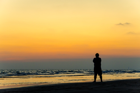 asana: Man silhouette stand alone on the beach