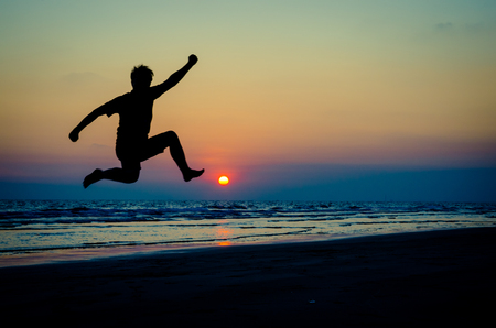 the case before: silhouette of a happy man jumping on a sunset on the beach
