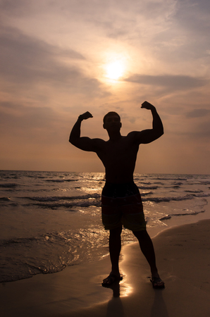 the Silhouette of a muscular man on the beach, sunset. Stock Photo