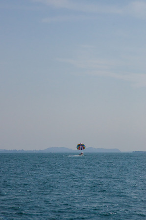 Tourists play colorful parachute sailing in the morning.