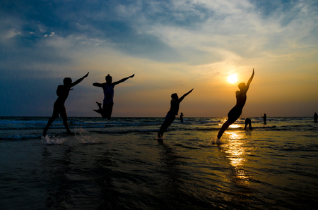 Silhouettes of young group of people jumping on the beach at sunset
