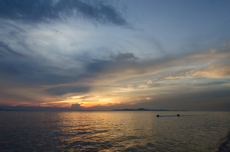 speed boat and banana boat into the sea with sunset