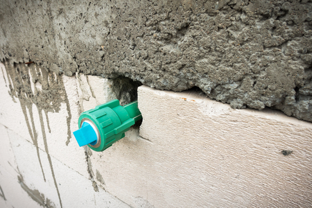 sewage system: Potable water pipe embedded in the block wall., Construction site.