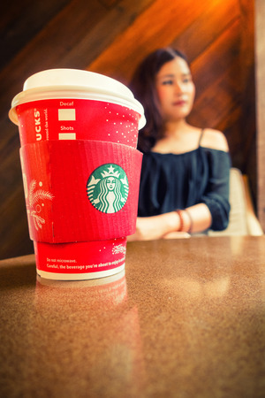 Bangkok ,Thailand-December 25 : Starbucks hot coffee on table with lady background on 25 December 2016 at Starbucks shop, Bangkok, Thailand.