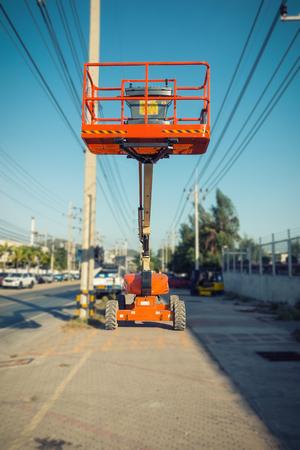 crane bucket: Lifting boom lift in construction site.