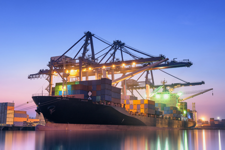 industrail: Cargo ship unloading container at twilight. Stock Photo