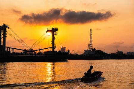Sunrise scene at Chaophraya river and passing of shipping boat. Stock Photo