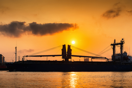 industrail: Sunrise scene at Chaophraya river and passing of shipping boat. Stock Photo
