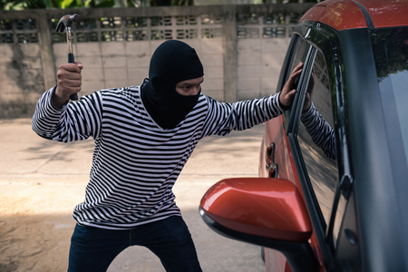 Car thief trying to unlock a car by screwdriver.