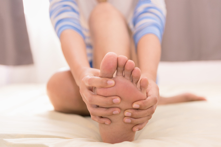 Young woman massaging her foot on the bed., Healthcare concept Stock Photo