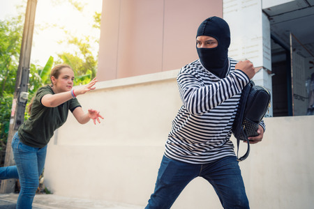 Robber snatching money and bag from women on the street., Thief, Robbery concepts Stock Photo