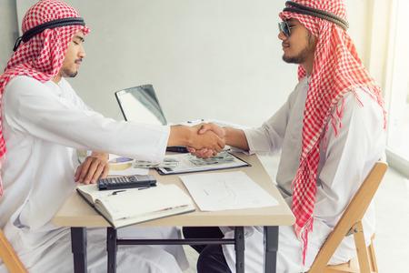 Businessmen arabian handshake each other when business dealing complete.