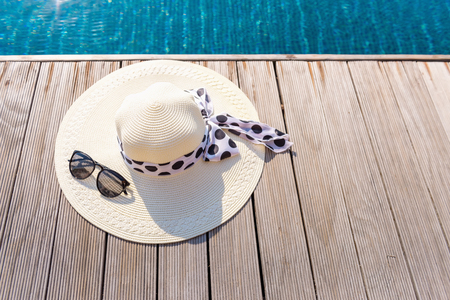 Straw sun hat and sunglasses on the terrace of swimming pool. Stockfoto
